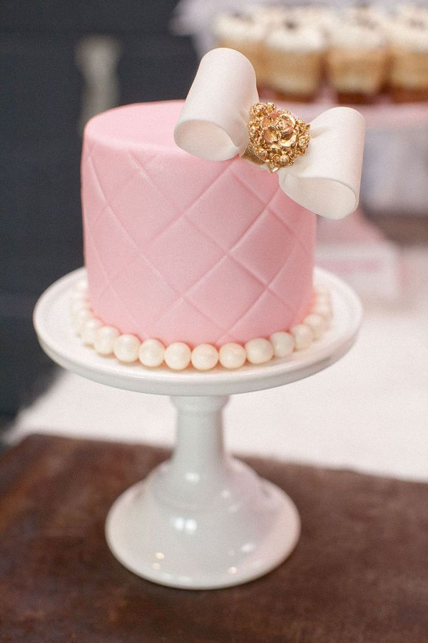 Pink cake with gold accents - the bow and pearls look is adorable