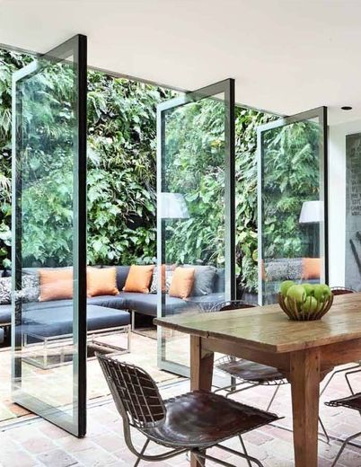 "Glass doors open to outdoor seating area with ""green walls"" - vertical gardens. :)"