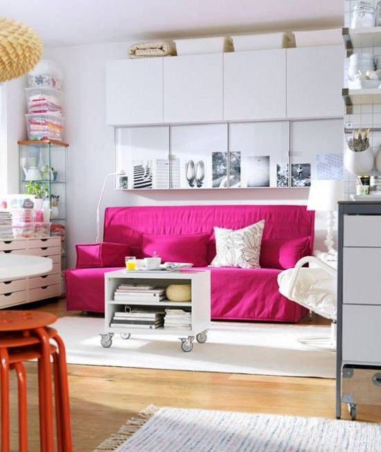 White bedroom Storage cabinets to the ceiling with a pink futon . Tons of storage for clothes and accessories in a Modern bedroom.