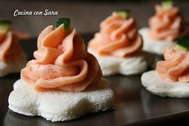 Mousse con salmone affumicato, un finger food semplicissimo e velocissimo da portare in tavola. Servito su crostini di pane bianco.