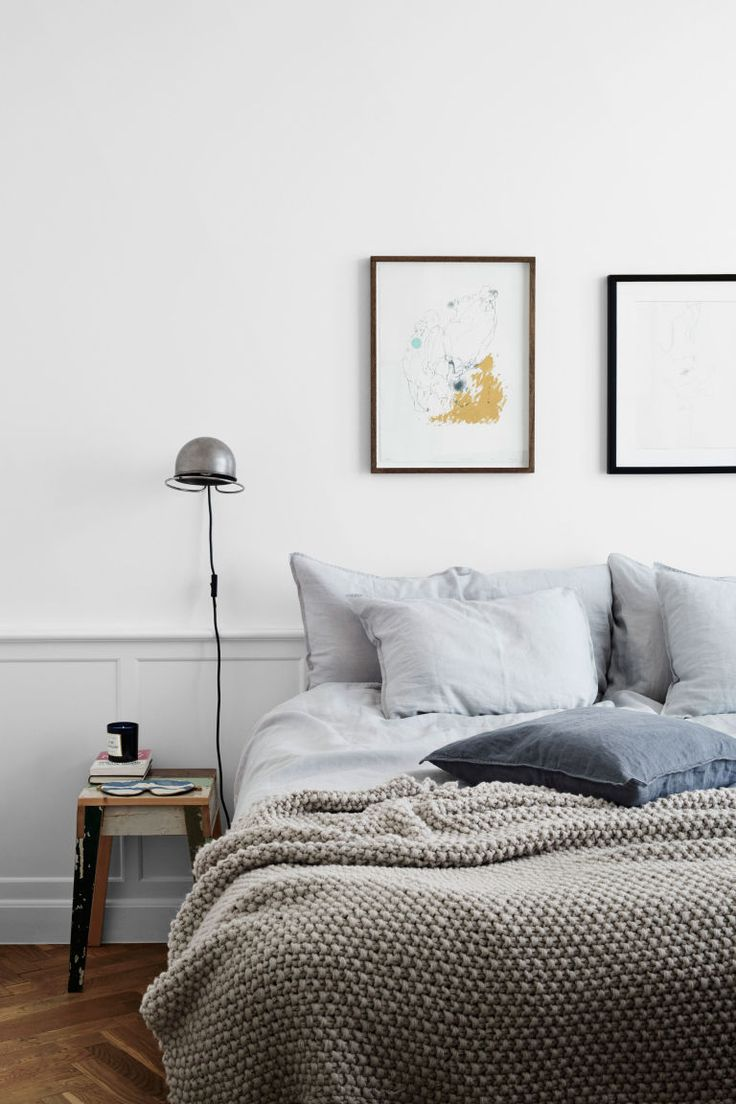 Minimalist neutral Scandinavian bedroom with vintage side table, nickel wall sconce and textured gray bedding.