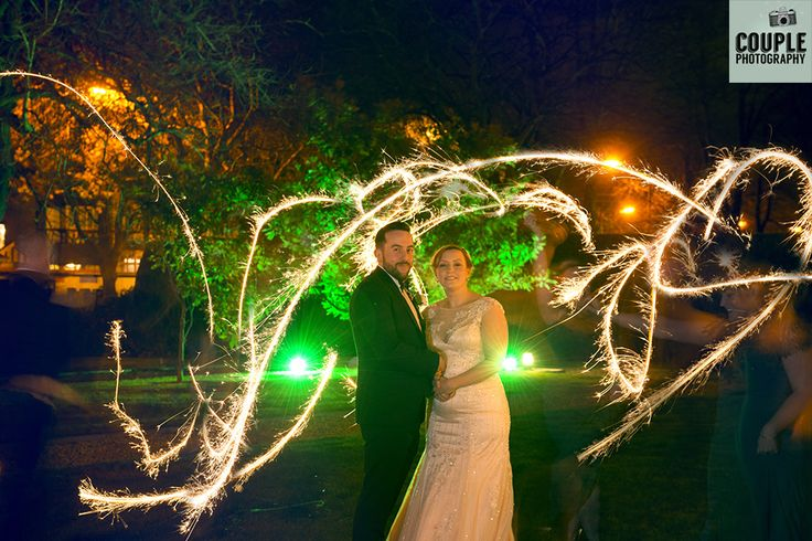 The bridal party light up the newlyweds with sparklers after dark. Weddings at Thomas Prior Hall, The Clayton Hotel by Couple Photography.