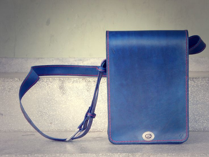 Handmade handstitched blue leather messenger bag with red stitches.