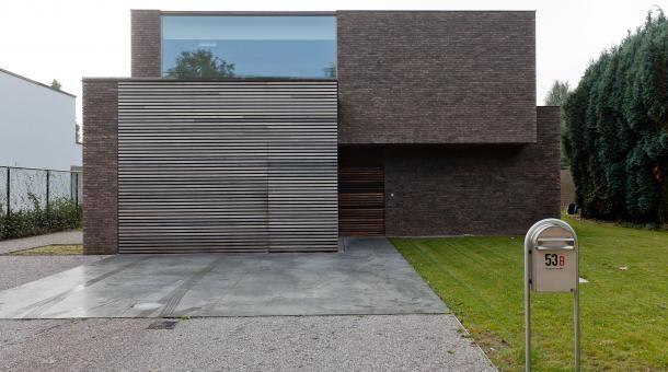 Combinatie van hout en baksteen. Zwevend volume zorgt voor een overdekte inkomzone.