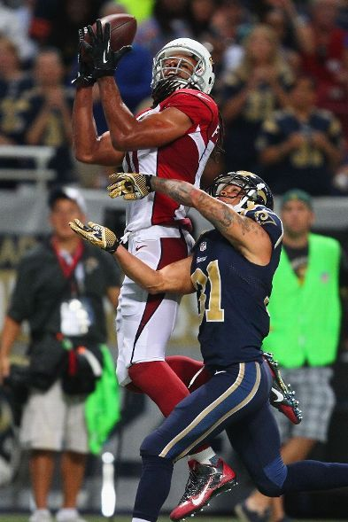 Larry Fitzgerald #11 of the Arizona Cardinals catches a touchdown pass against Cortland Finnegan #31 of the St. Louis Rams at the Edward Jon...