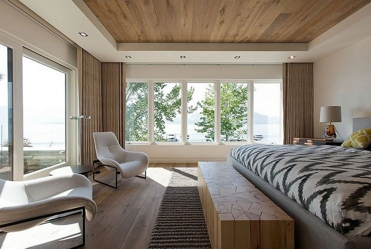 спальня с большим окном и видом на озеро