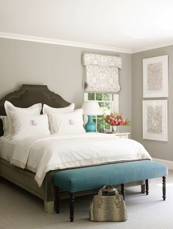 Bedroom with gray walls, a pair of vertically stacked gray abstracts  with a gray and ivory damask roman shade. The bedroom features a dark taupe velvet bed layered with monogrammed bed linens. A long teal bench at the foot of the bed over beige carpeting