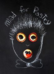 hand drawing of crazy confectioner with mini pastry over slate