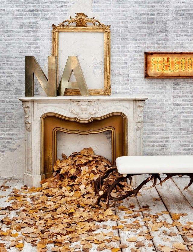 Ahora que se acerca la Navidad, tener una chimenea es un auténtico filón decorativo. Máxime si hay niños en casa. Este ambiente la utiliza como fuente de unas bonitas hojas doradas que cubren el suelo de madera a modo de alfombra. Los tonos blancos, grises y dorados, colorean una imagen otoñal perfecta en la que la chimenea es la reina.