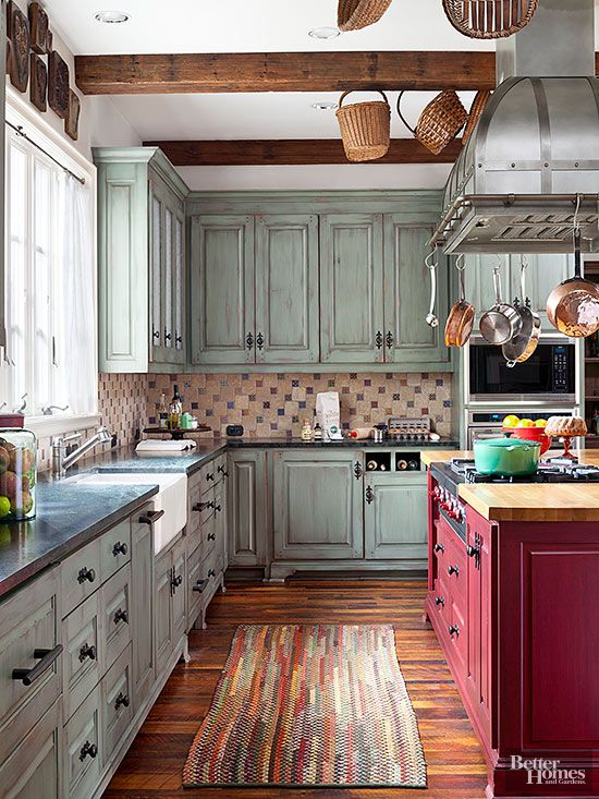 Rustic kitchens should appear as if they were furnished over time. This kitchen does so with a rough-texture tiled backsplash that pulls together the room's red, green, and brown tones. Ceiling beams, wood floors, and antiqued cabinet finishes play happily with shiny copper pans and dangling baskets that contribute at-hand utility.