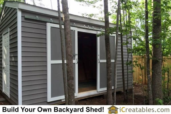 Sliding barn doors installed on shed by hanging them on for Hanging barn door in house