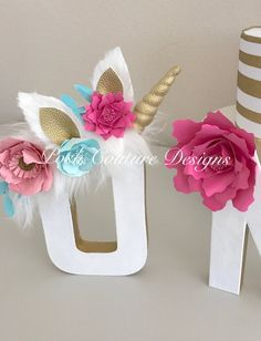 Letras decorativas brancas, com adereços em rosa, azul e dourado.