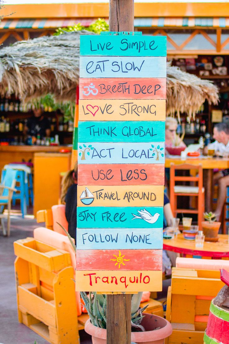 Tranquilo ethical bar in Perissa, Santorini with colourful mantras and slogan signs on a board.