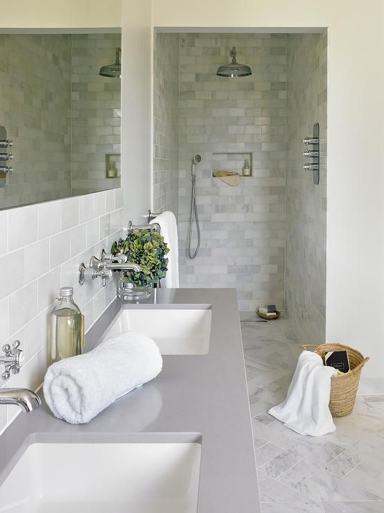 White and gray bathroom boasts a white dual washstand topped with gray quartz fitted with his and her sinks placed under vintage cross handle faucets lining  gray subway tiled wall.