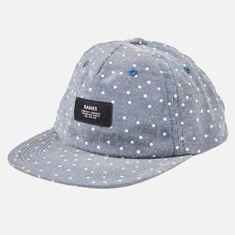 Light weight chambray unstructured cap with discharged yardage print, plastic snap back and recycled polyester woven labels.