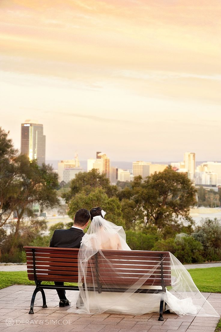 Amazing sunset over the Perth city skyline. Romantic wedding photo of a Bride and Groom cosying up on a bench Location ~ Kings Park, Perth Photography by DeRay & Simcoe
