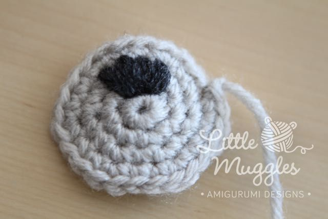 Sew the nose on with charcoal yarn. Tie a tight knot on the back side.