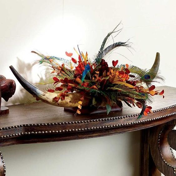 Bring the elements of the great cattle drives and wide open plains to your wedding with this rustic peacock and longhorn centerpiece. | King Ranch Saddle Shop