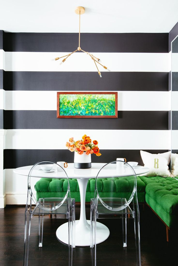 The L-shaped tufted bench makes a vibrant statement against the bold, thick wall stripes in this breakfast nook. The kelly green coloring of the bench compliments the floral wall art mounted above. Clear plastic chairs are seated on the opposite side of a modern oval dining table. An orange floral centerpiece and brass light fixture finish the chic design.