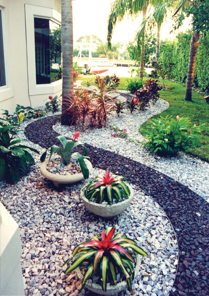 The owner of this Palm Beach Gardens, Florida home wanted a minimalist, clean-lined garden. Pamela Crawford designed curves of different-colored gravel, accented with tropical plants. See more clean-lined south Florida landscapes at www.pamela-crawford.com. Servicing all of Palm Beach county, including Boca Raton, Delray Beach, Wellington, town of Palm Beach, Palm Beach Gardens, and Jupiter.
