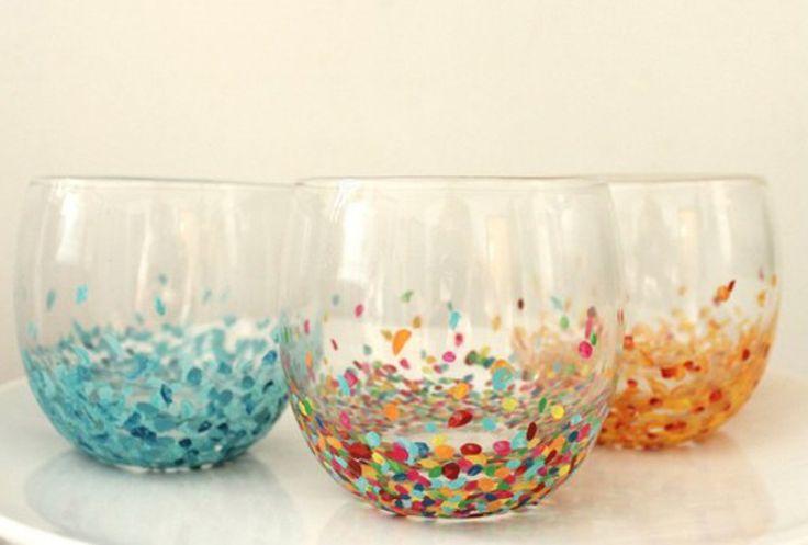 Simpele glazen versieren met confetti. Zodra je de confetti op de glazen hebt geplakt, ga er dan met een transparant laagje overheen (bijvoorbeeld nagellak).