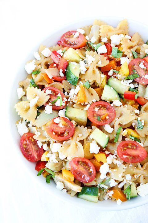 Salade de pâtes avec un concombre, des tomates, de la féta, des poivrons, du vinaigre balsamique...