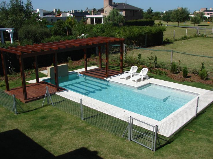 Piscina familiar pergola madera deck muro con for Cascada piscina