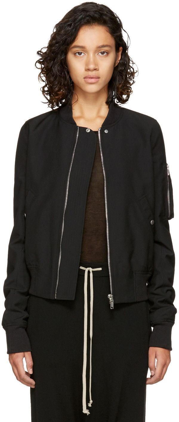 Long sleeve wool bomber jacket in black. Rib knit stand collar, cuffs, and hem. Zip closure at front. Welt pockets at waist. Utility pocket at upper sleeve. Buttoned patch pockets at interior. Fully lined. Silver-tone hardware. Tonal stitching.