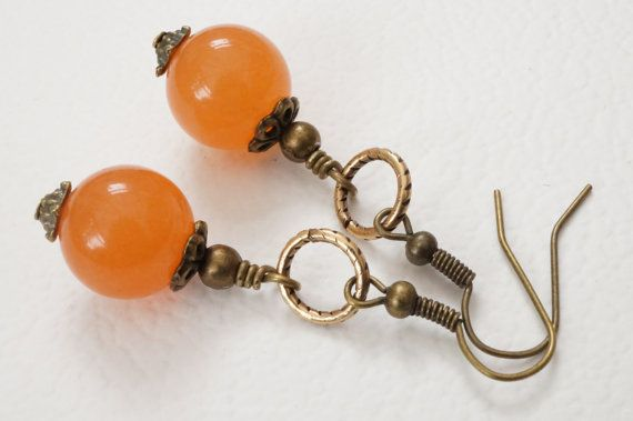 Handmade gemstone earrings featuring 12mm orange agate with antique bronze elements.  Juicy orange agate with antique bronze bead caps, earwires and small beads wrapped with brass wire onto Trinity Brass etched rings.  Overall drop 5cm.  Many of my photos are taken close up with a macro lens. Please check measurements before ordering to make sure you are happy with the size.