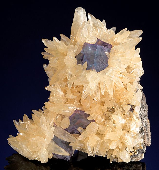 Attractive specimen featuring golden Calcite crystals surrounded blue Fluorite cubes! This is a eye catcher and the Calcite tips are complete & in excellent shape. The Fluorite cubes are surrounded on all sides, making for a beautiful combo & display. From the Bethel Level Green Tracts, Cave-in-Rock District, Hardin County, Illinois. Measures 5.7 cm by 5.3 cm by 4 cm in total size. Circa 1950's to early 1960s - Ex. Bynum Mineral Collection / Mineral Friends <3