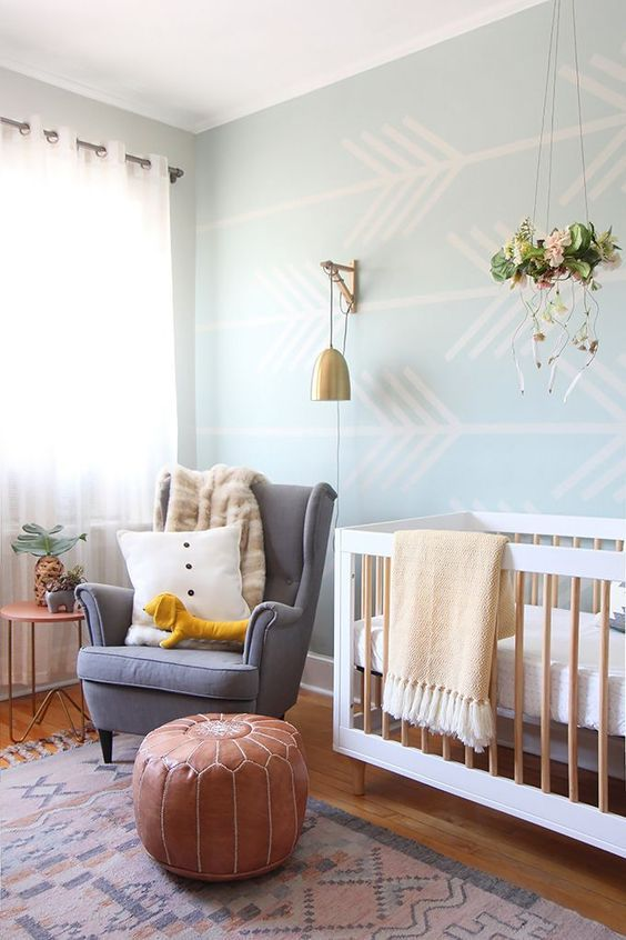 boho nursery with pastel blue walls, brass light, modern crib and a Moroccan pouf