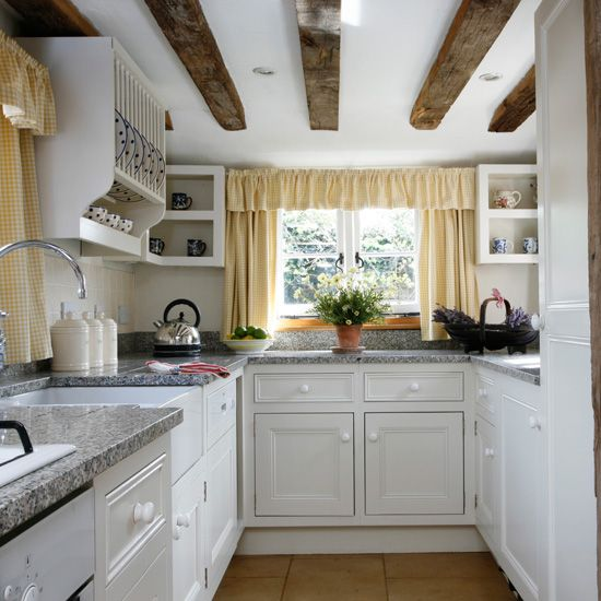 Small kitchen with exposed beams, granite worktops, white cabinetry, open shelving, plate rack and yellow gingham curtains