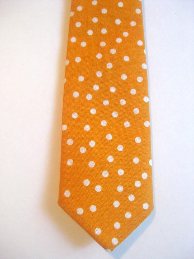 "Do you have a little guy that wants to be just like his Daddy? Our adorable handmade neck ties feature an adjustable neckband with velcro closure, to help make it quick and easy to put on / take off. { DETAILS } : - Orange + White Polka Dot fabric - Size newborn-12 months - Tie length is approx 8 1/2"" long - Ties come pre-tied and can be adjusted to make them longer / shorter. { CARE }: Ties are washable - gentle cycle or hand wash. Lay flat to dry. Iron lightly to smooth any wrinkles…"