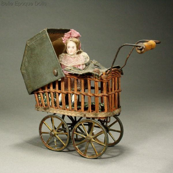A wooden-floored carriage with metal-spoke wheels has woven wicker sides, wire handle with wooden hand-grip, original leather-like sunshade, cover and