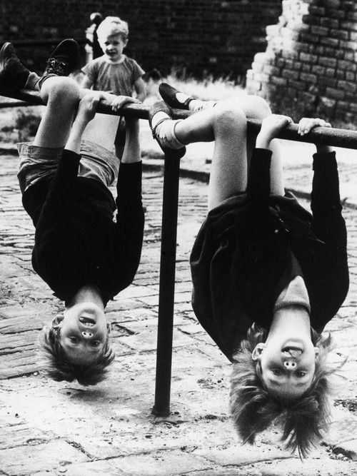 Shirley BAKER :: two children have great fun hanging upside down off a low rail in stockport, 1966 [original]
