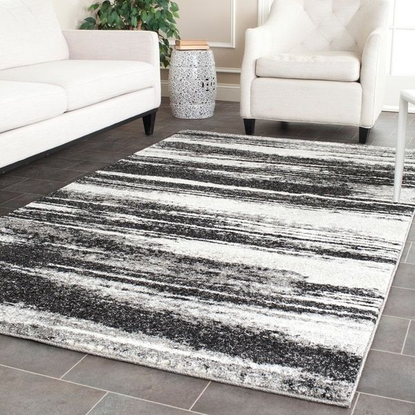Recall mid-century modern style with this 8'9 x 12' rug from Safavieh's Retro Collection. Featuring an Art Deco inspired pattern of light and dark grey, this rug easily coordinates with most existing