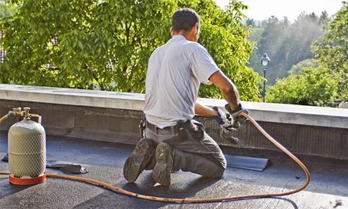 Flat Roof Repair and Installation Services  What is Flat Roofing?  Flat roofing typically consists of multiple layers which is laid down in a series of layers and then torched down and heat welded. This type of roofing material is known as Modified Bitumen Membrane. The membrane is made of a fiberglass layer between layers of rubberized asphalt which is then topped with a layer of small ceramic stones. This top layer helps to protect the roof from the elements as well as reflect heat and UV…