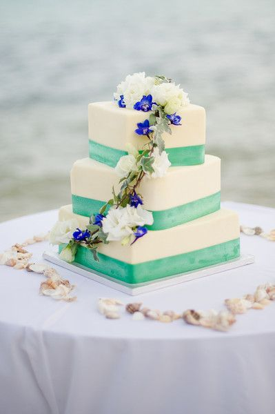 Beach wedding cake idea - three-tiered square shaped wedding cake with green ribbon and cascading white and purple flowers  {Palm Beach Photography, Inc.}