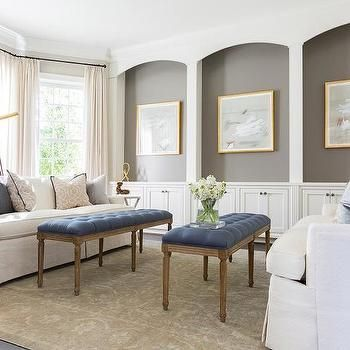 Chic Living Room Features A Wall Of Arched Niches Painted Gray Lined With Art In Gold Picture Frames Placed Over Built Cabinets
