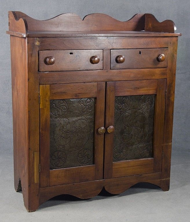 Mid 19th century. Having scalloped backsplash (possibly re-attached) above two dovetailed drawers. Over two tin-paneled doors with fylfot design in center. With simple scalloped skirt and carved boot jack ends in solid single board. Poplar secondary. Refinished with repairs and replacements.