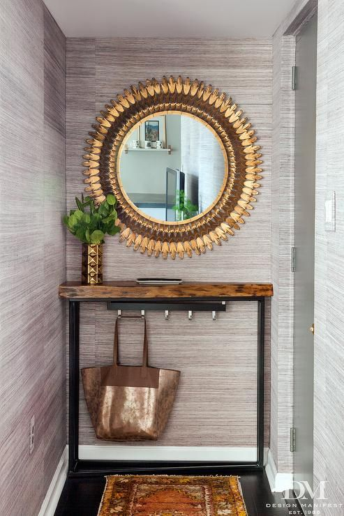 Gray and gold foyer features walls clad in gray grasscloth, Scalamandre Haiku Dogwood Wallpaper, lined with a rough hewn console table and a Anthropologie Sundial Mirror.