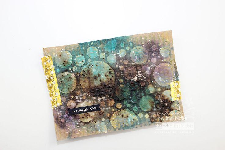 Decorate using washi tape strips, sewing and a sentiment sticker. The layering of all these different ink types gives a wonderful end result. Think how amazing this would look on a canvas. The gold Delicata ink reacts with all the other inks giving this piece a wonderful shimmer overall. How will you layering inks together? …