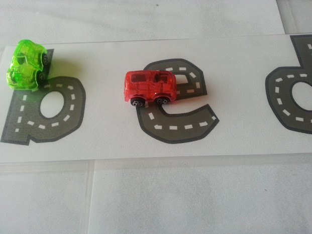 Cars/alphabet learning playdate - cut letters of the alphabet out of black construction paper and use white crayon to make them look like roads.  Have the kiddos trace the letters with their cars, saying the letter, if they're able and willing.
