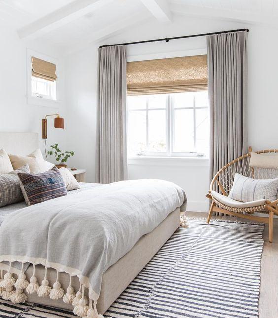 Gray throw blanket with cream poof tassels, grey striped rug, tan shocker chair, neutral bohemian clean trendy bedroom