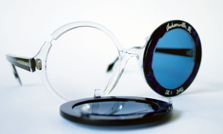 Custom-made frames/sunglasses produced and designed by General Eyewear and made in General Eyewear's London workshop. Optical frame has a clear front and blue sides. Blue rims with sun filtres clip onto the frame and have been engraved with commissioning client's name.