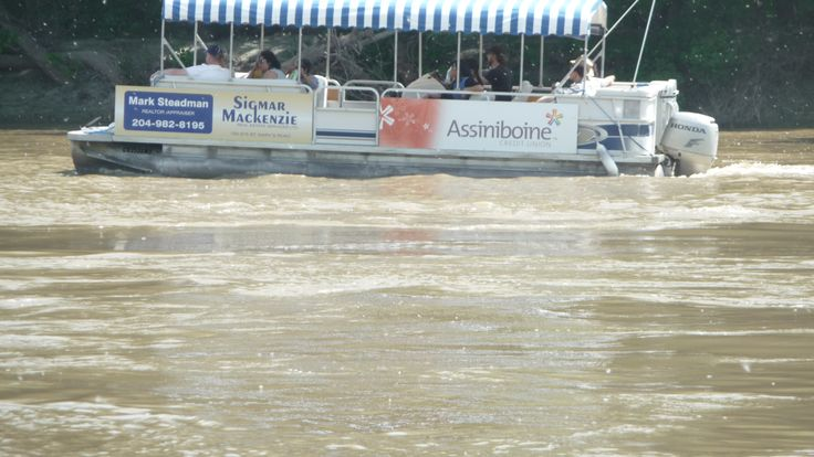 Splash dash water Tour boats along Assiniboine River at The Forks during hot summer July day