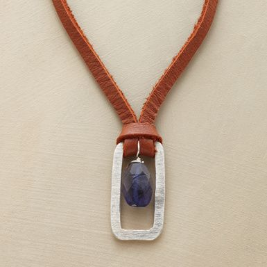 """Framing a faceted iolite oval, a brushed sterling window is knotted on a brown leather lariat, with a sterling button and loop closure. Handcrafted in USA. Exclusive. 17""""L."""