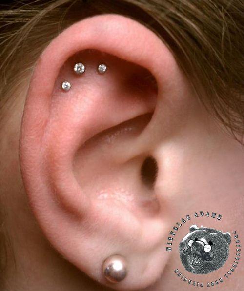 Triple cartilage piercing by Nicholas Adams
