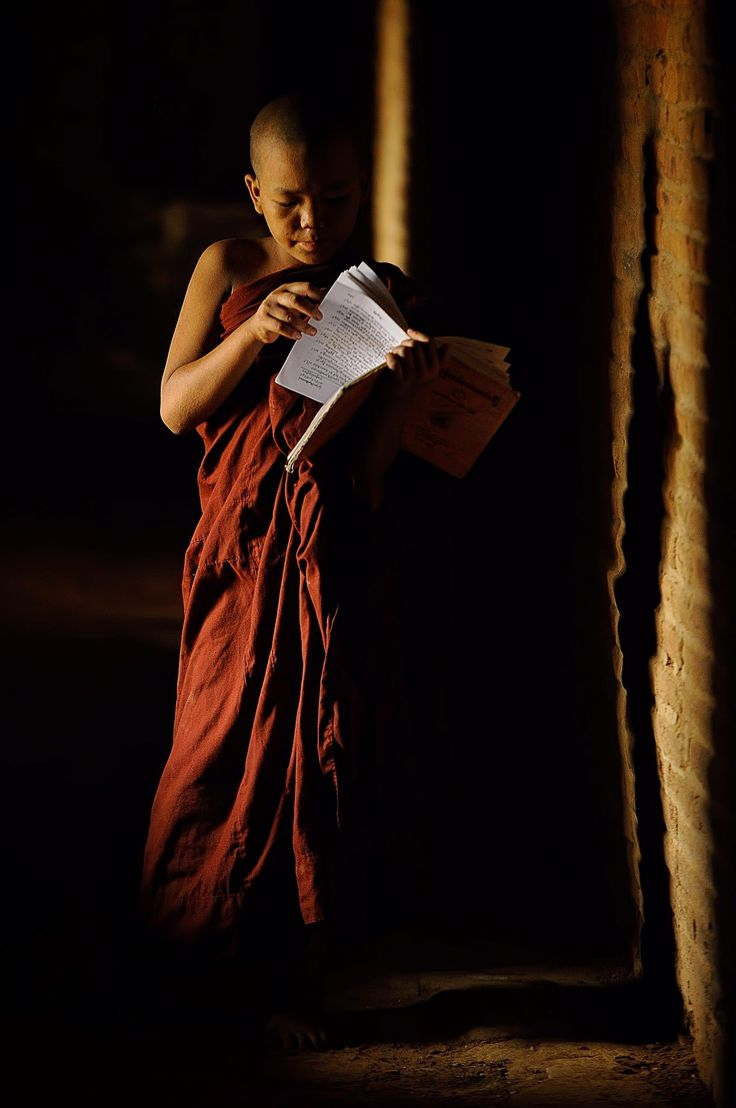 A novice monk in Bagan studying the Buddhist bible while also casting his shadow on the wall of the temple's hall way. Photo by Vichaya Pop.