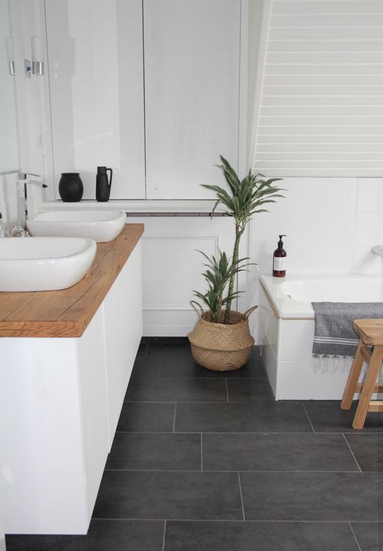 our new DIY bathroom. Renovation on a budget is finished!;) i like the combination of cold elements like white walls and grey floor with warm elements like wood and plants designdots.de I Badezimmer selbst renovieren. So sieht unser Badezimmer jetzt aus, graue Fliesen, weiße Wände ohne Fliesen, selbstgebauter Waschtisch mit einer Holzplatte aus alten Eisenbahnschwellen und viele Pflanzen;) mehr dazu auf designdots.de